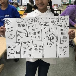 Students drew their buildings in Sharpie marker first. Here is a student holding up her artwork with several buildings drawn in Sharpie; each building has a unique face and windows