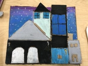 students cut out different shapes from cardboard then arranged the shapes to look like houses, schools, light houses, etc. and glued them to a larger piece of cardboard. Then they colored in the cardboard with oil pastels to show the color of the building, the windows, and the sky