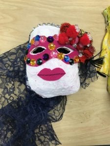 student mask that has a light pink round face, a lace veil or hair, pink lips, a pink mask that covers the eye area with jewels around the eyes