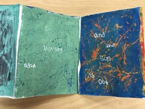 """two paintings next to each other, one is green with small blue specks and the other is blue with orange splatters, they say """"Morning again...and the sun is out"""""""