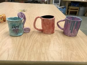 three student made ceramic pieces that look like mugs