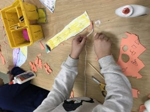 student working on gluing a string and a wooden dowel to his paper rectangle kite
