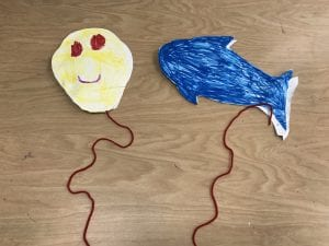 A circle was cut from paper and colored to look like a face with heart shaped eyes and there is a red string glued below it. There is a dolphin shape cut from paper, colored blue, with a red string hanging below it.