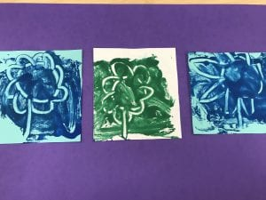 three smaller papers with blue and green paint and a white flower drawn on each one have been glued to a larger purple paper.