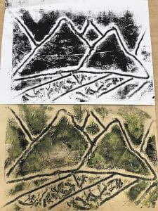 One artist created two different copies of his design; it shows a mountain range with fields of grass below; one paper is printed with black ink and the other with yellow