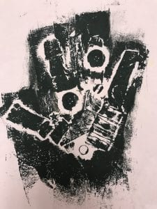 One print looks like a hand, made out of scraps of different textured fabric and buttons; it is printed with all black ink