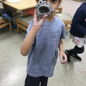student holding his clay creature; his clay creature has several eyes and an open mouth