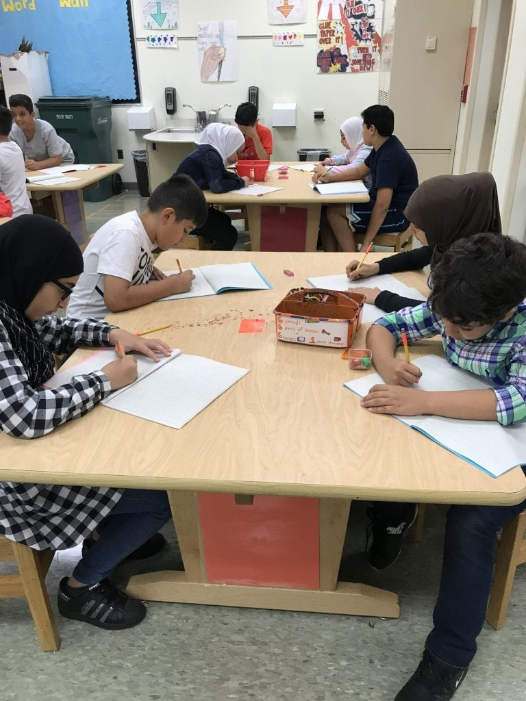 Here are four students gathered around a table; they are each drawing with pencils in their own sketchbook.