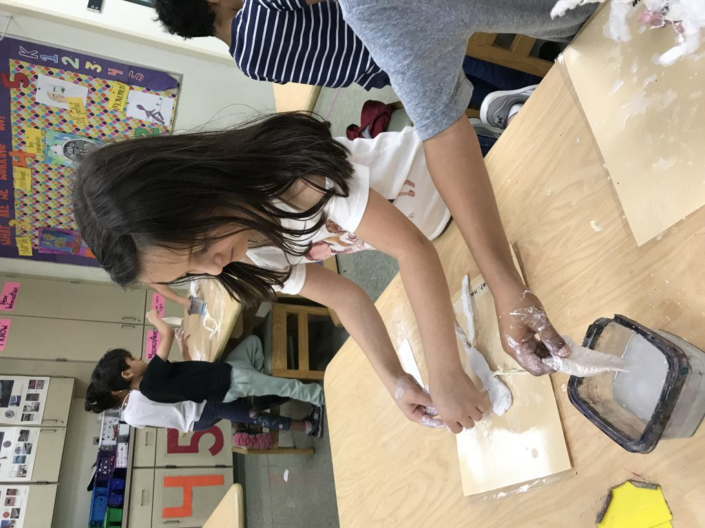 Here students are dipping strips of plaster cloth in water and wrapping them around their wire and tape sculptures.