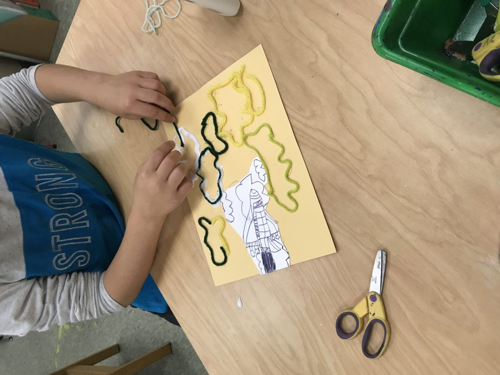 Here a student is gluing don pieces of string to show the clouds in the sky. They also have a piece of styrofoam to show an airplane.