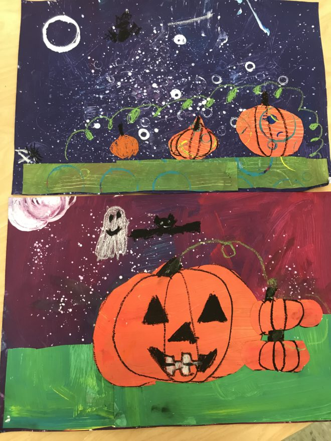 Hre are examples of students' finished pieces; they all have green grass, orange pumpkins, and a purple sky, but their colors are all slightly different and some have textured lines or stamps on them. One student drew faces on the pumpkin and added a ghost and a bat in the sky.