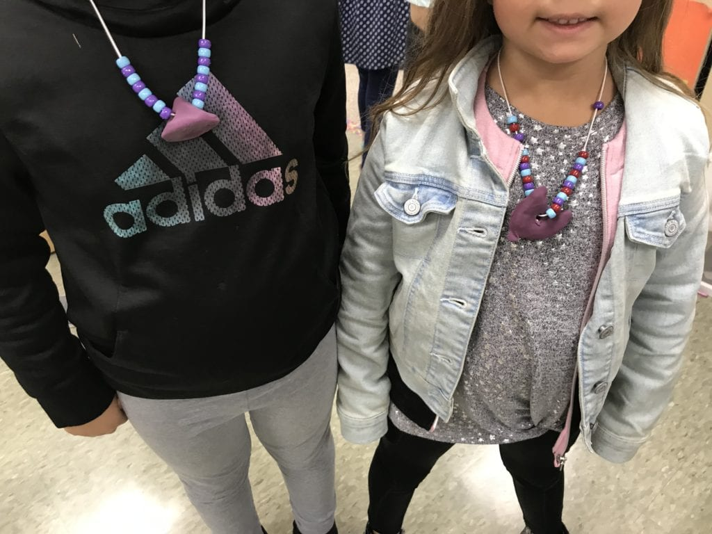 Two girls are modeling their necklaces; they both have a purple large clay bead in the center and have a pattern of smaller beads on the sides of it