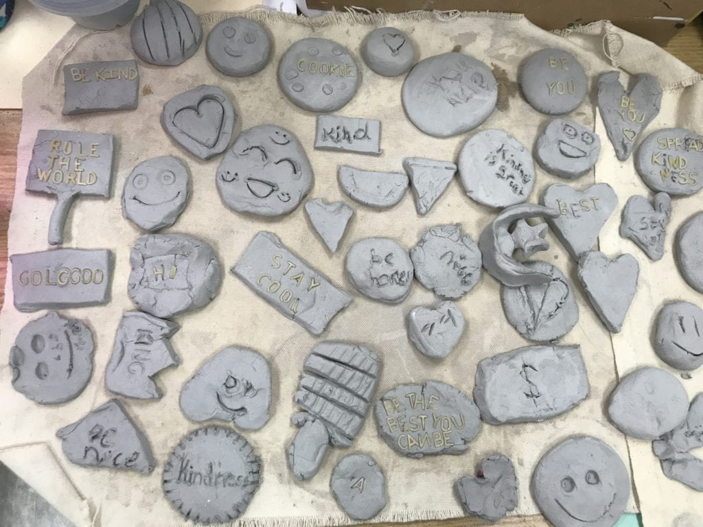 Here are some of the clay pieces; they are all gray still and are different shapes such as a smiling emoji, a heart, a popsicle, a pumpkin, a circle with the word kindness in it, and a slice of pizza.