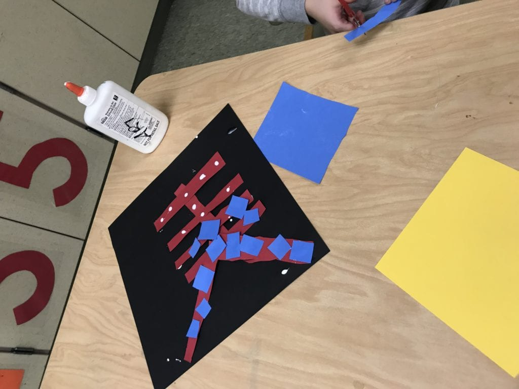 Here a student is cutting a blue paper into strips and has some blue and red rectangles glued to their black paper.