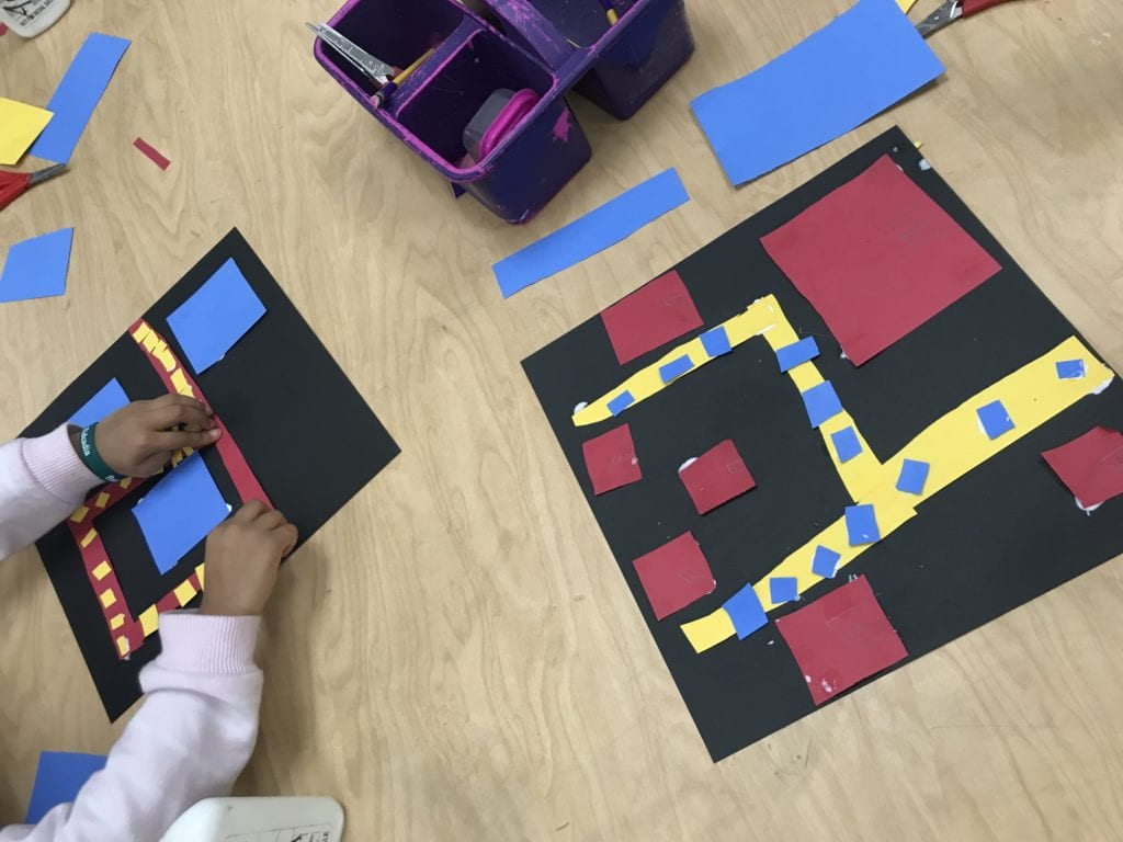 Here are two students working; onw hs gluing down yellow small squares on a red rectangle to look like cars on a road.