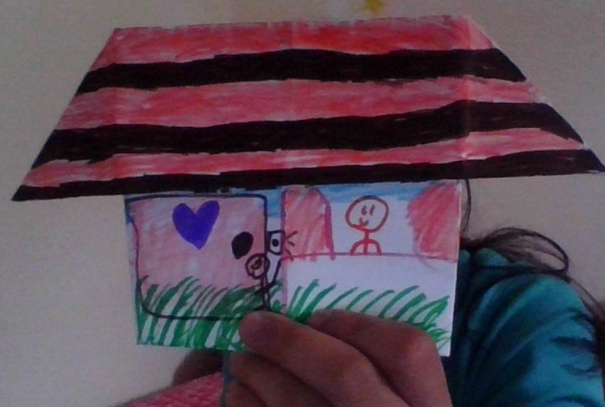 folded paper origami house with striped roof, door, and window