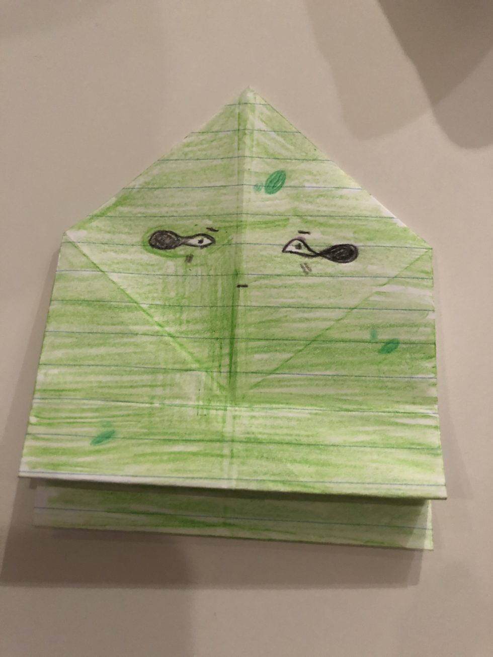 folded paper origami frog colored green with black eyes