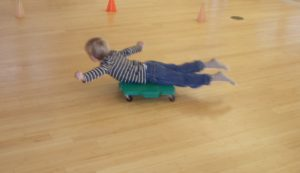boy doing airplane on scooter board