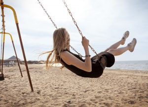 Young Woman On Swing by Beach