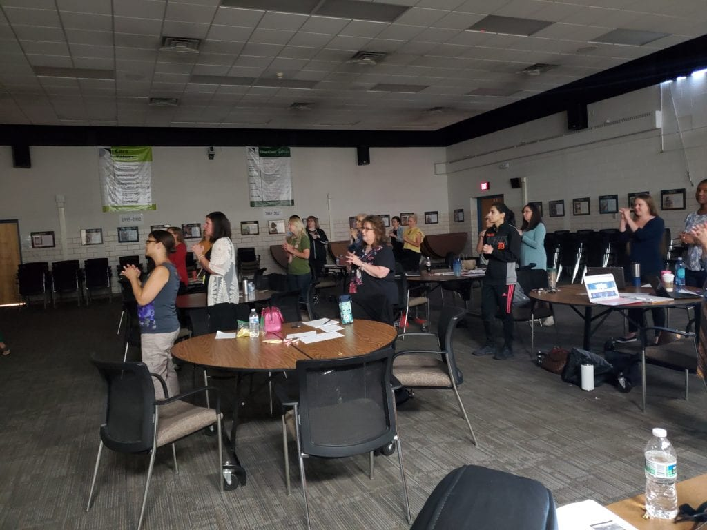 teachers standing using hand gestures to learn about the brain during a SDI training