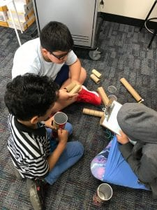 3 students use cardboard to create projects