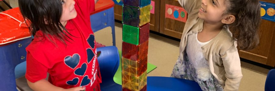 girls build a tower with colorful blocks