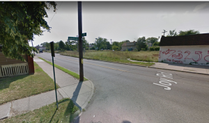 Google Image of the corner of America St. and Joy Road. Shows intersection with building covered in graffiti.
