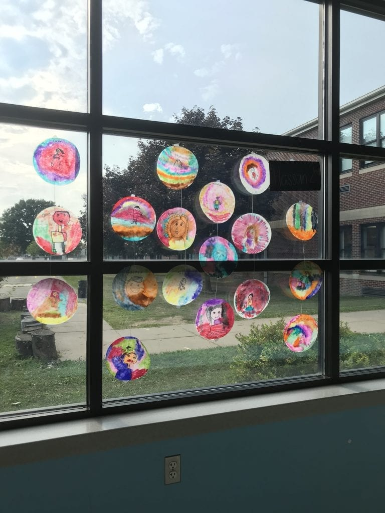 Here is a window with some of the dots hanging in it; the dots are colorful and are hanging 3-4 on a string in front of a window.