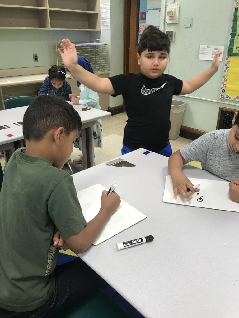 This student is posing by holding his arms out while two students draw him with white boards and markers.