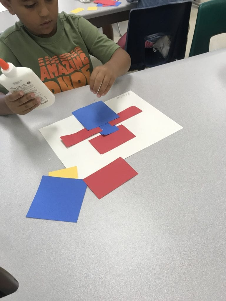 Students glued primary colored rectangles to their papers to make a design that they liked.
