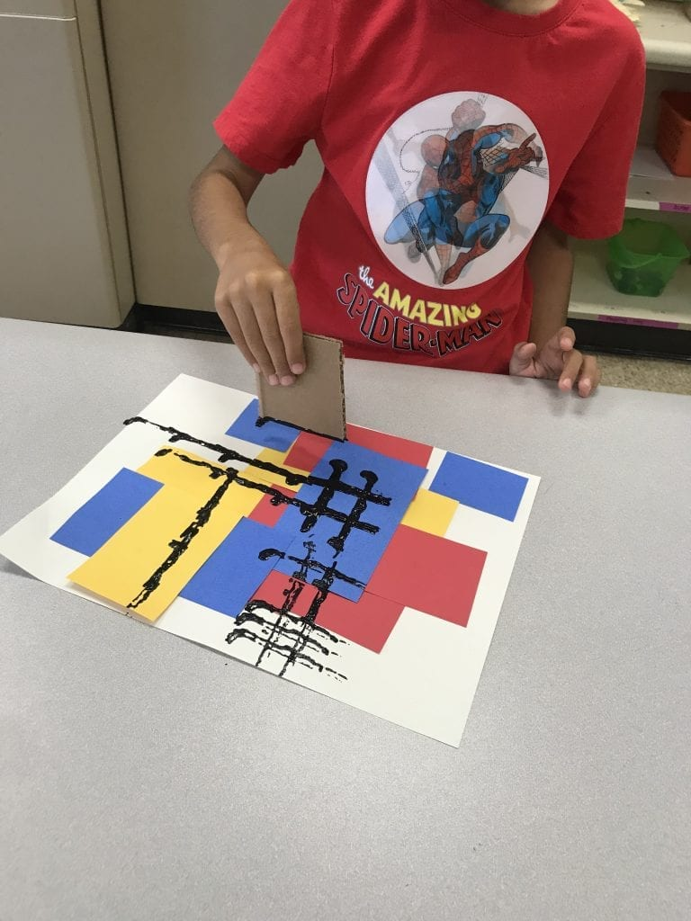 This student is using a piece of cardboard to stamp black lines on his paper that also has red, yellow, and blue papers glued to it.