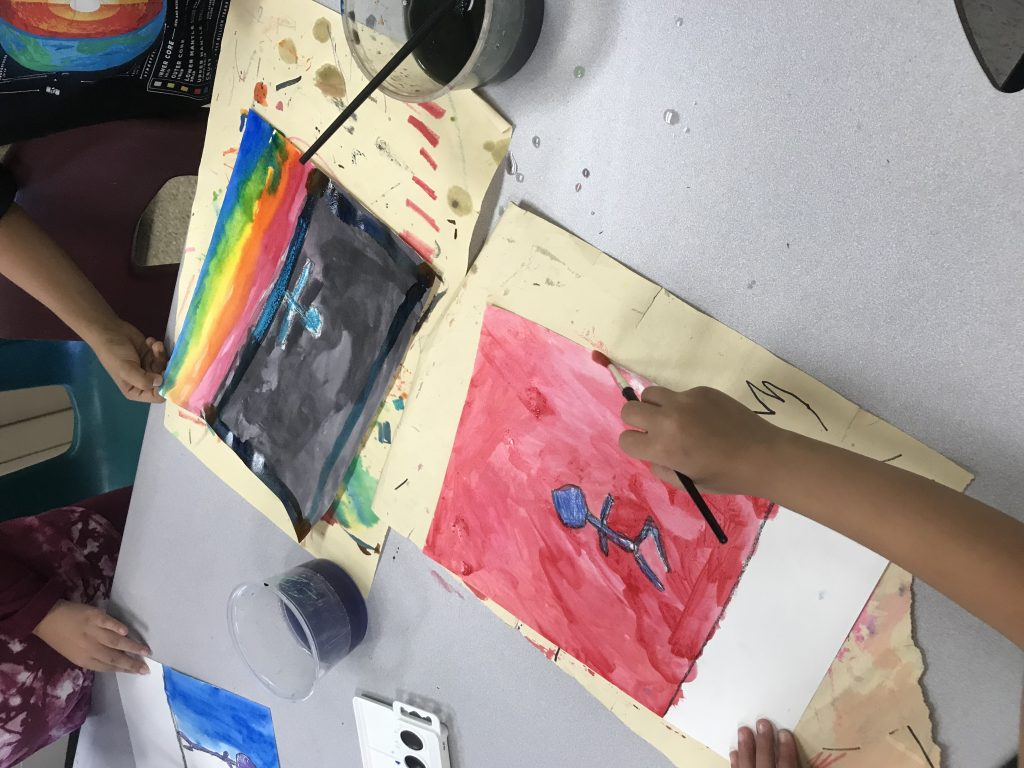 Here two students are painting behind their drawings of a colorful silhouetted person running