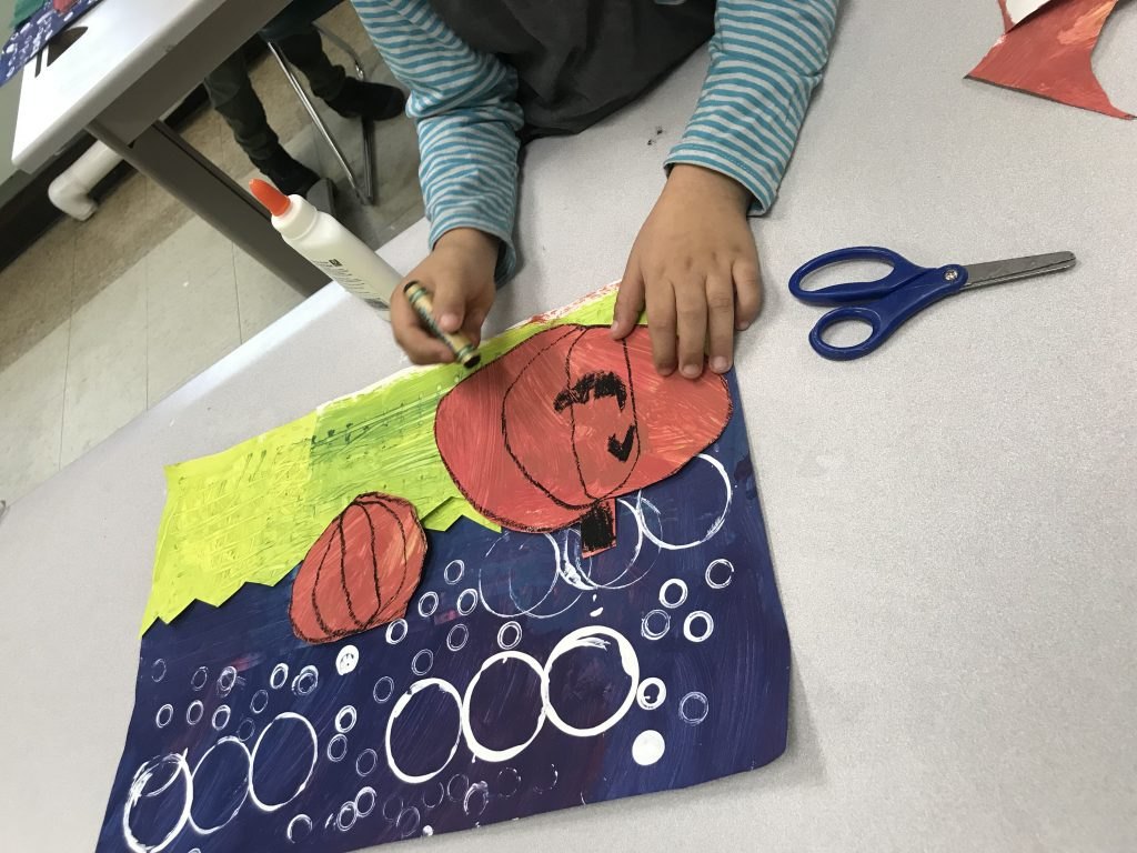 They each cut from their green paper lines for grass, round shapes from their orange paper for pumpkins, and glued them to their pupLE BACKGROUND TO SHOW THE NIGHT SKY.
