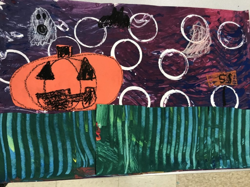Students glued green painted papers to the bottom of their papers to show grass, orange papers were cut to show pumpkins and were glue to the grass, and the sky is their purple paper.