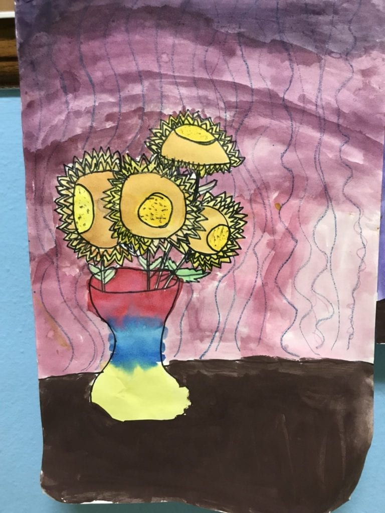 This painting shows a brown table, a primary colored vase, and four sunflowers in the vase that are all facing different directions.