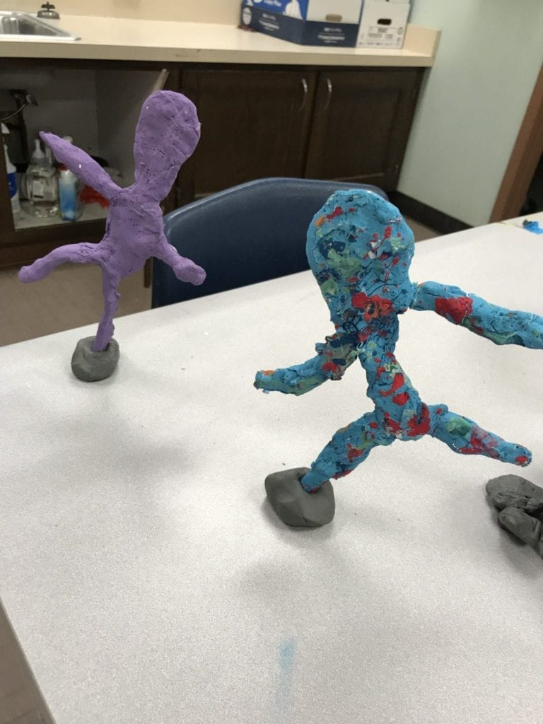 Here are two student sculptures; one is blue with spots and is leaning forward on one foot with both arms stretched out, and the other is all purple and is also standing on one foot.