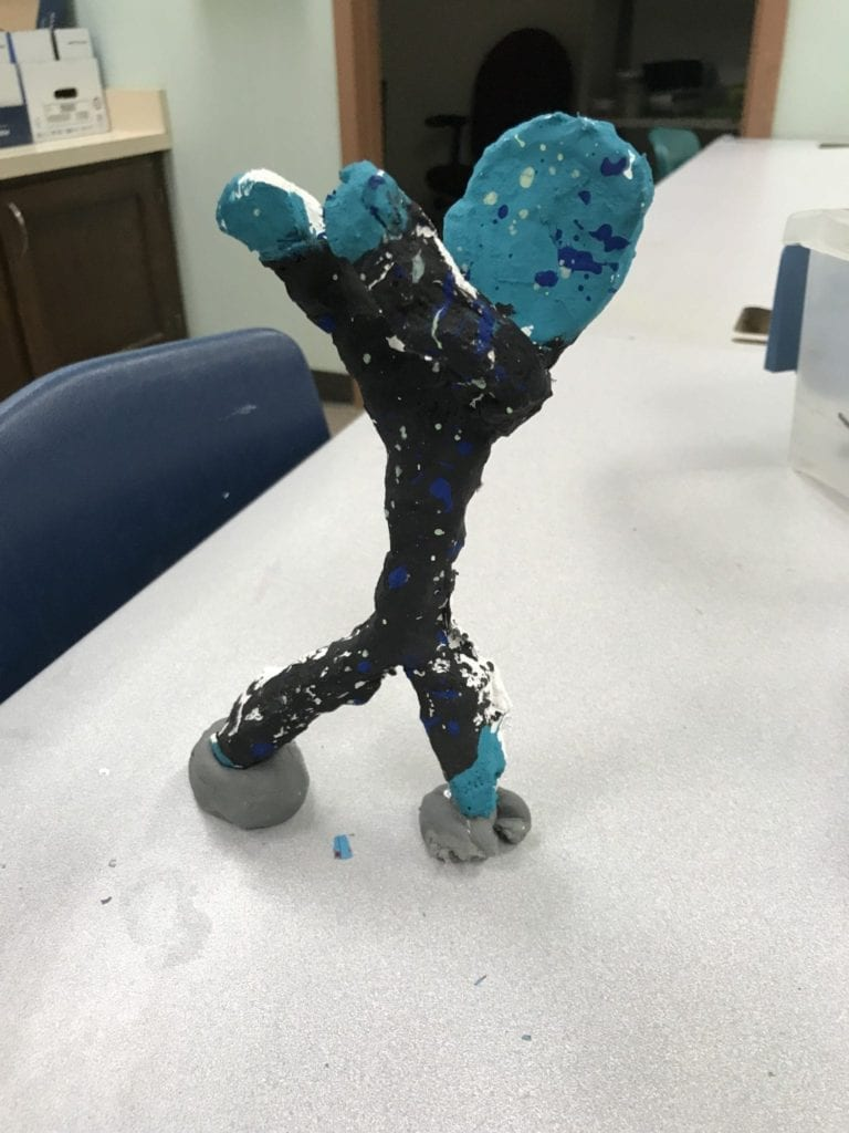"This sculpture is black and teal and is standing on two feet with both arms stretched out to the left in a ""dab"" position"