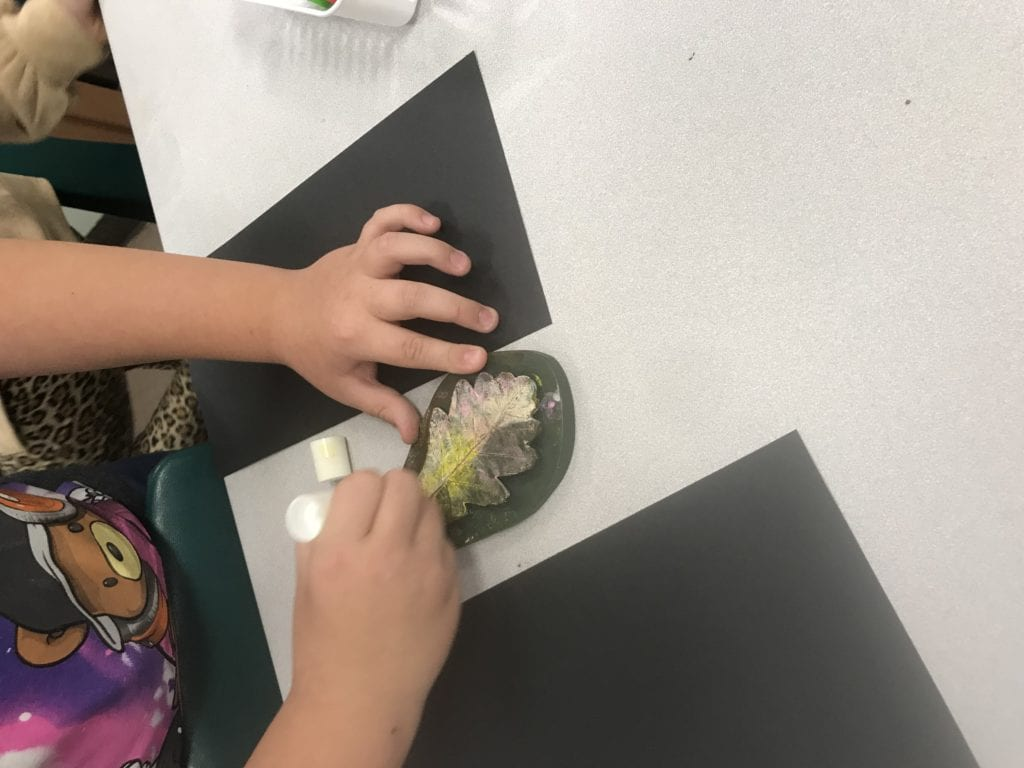 Here a student is coloring on a rubber leaf with a paint stick; they are using white and yellow.