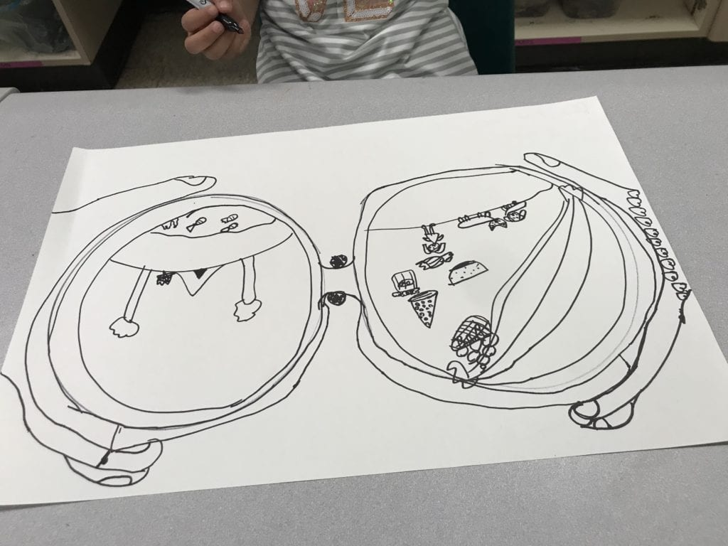 Here is a student drawing with black Sharpie; they drew a large pair of binoculars with a tent adn trees, a rainbow, and other small objects inside of the lenses.