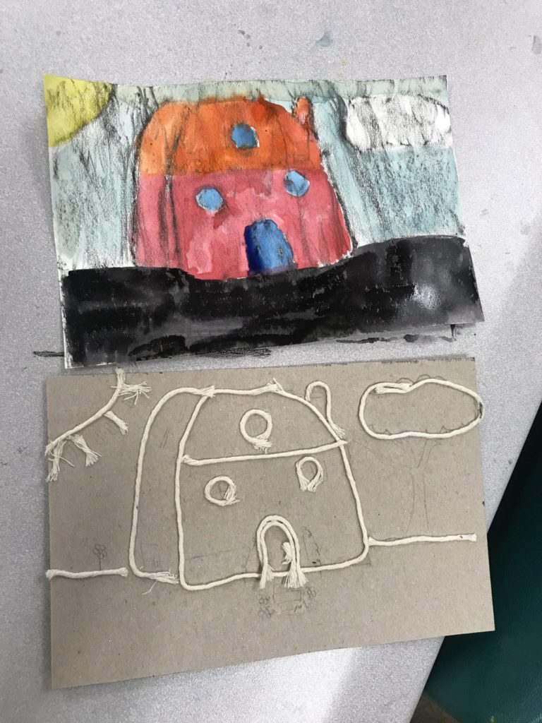 Here is a student's collagraph plate that shows a house and then her crayon rubbing all painted in above it