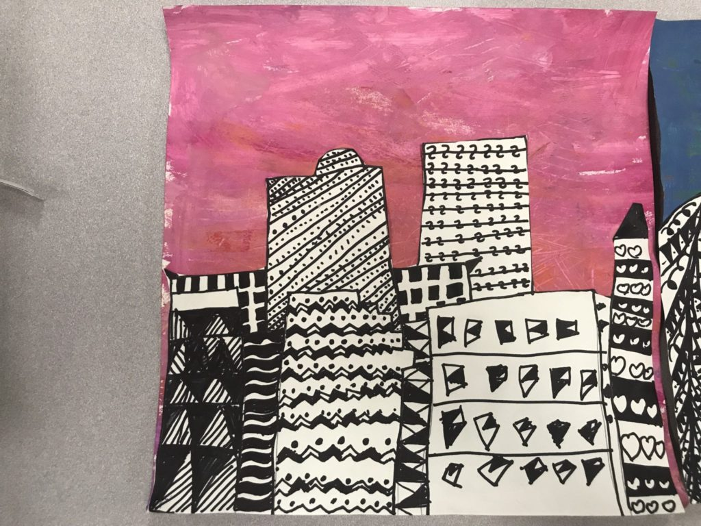 Here is a student's artwork that shows a series of buildings, most of them rectangular in shape, and they are all filled with different patterns ranging from straight ines to zig-zag lines and small dots