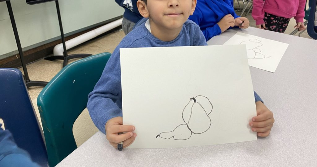 Here is a student holding up his drawing of pears, without shadows,