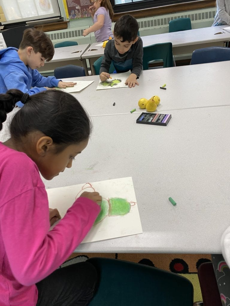 students leaning over their papers drawing pear with chalk