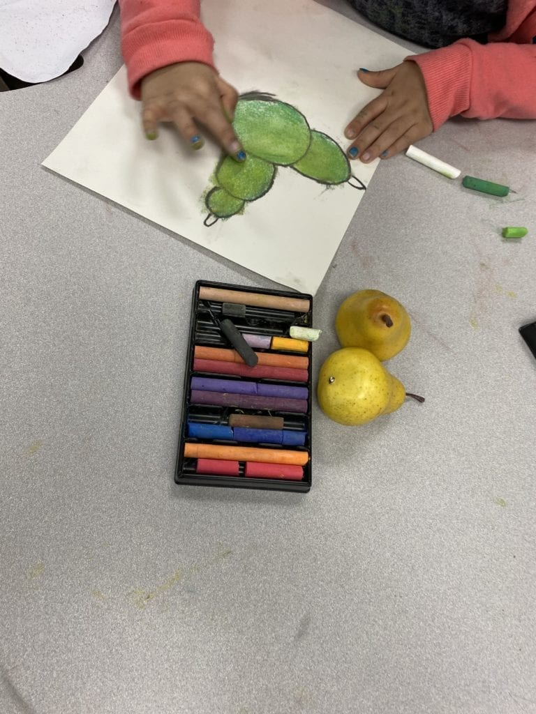 a student using her finger to smear or blend the chalk on her pear drawing
