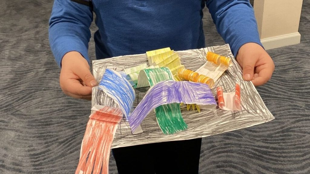 Image of a young boy holding a paper sculpture; there are colored pieces of paper glued to a black paper so that they are curled, folded, and popping off of the paper