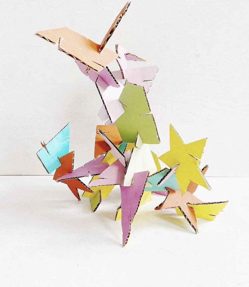 Several pieces of painted cardboard stacked/fitted to each other to create an abstract sculpture