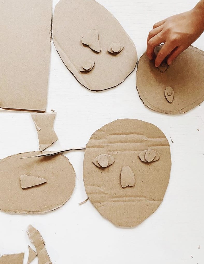 hands laying pieces of cardboard together to look like faces