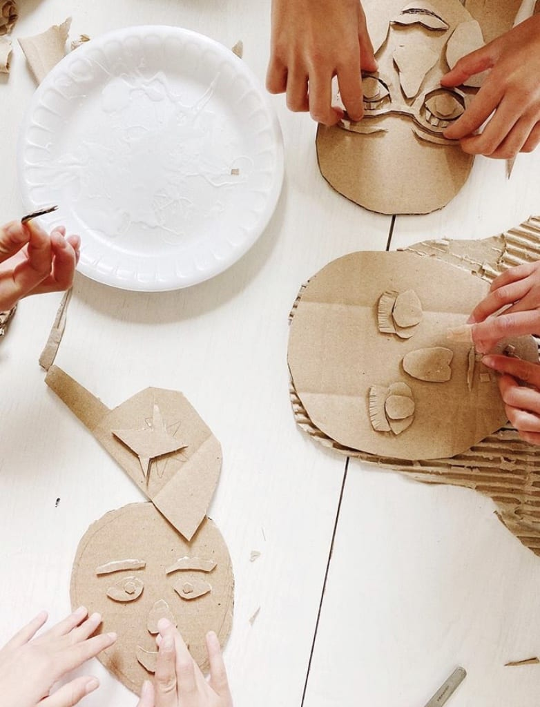 hands working on gluing shapes to cardboard to look like faces