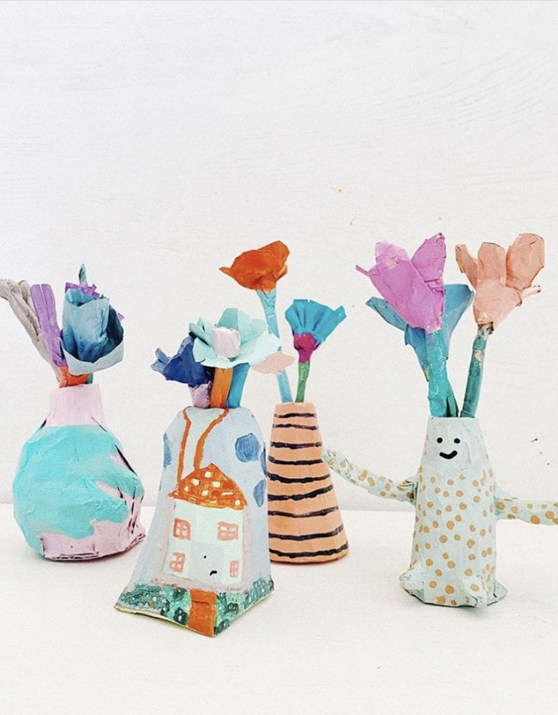 Four different shaped vases with fake flowers coming out of the top