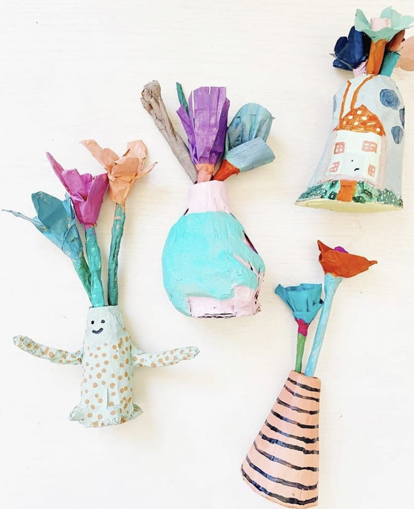 four different shaped vases made from paper and tape with flowers coming out of the top, also made out of tape, everything is painted colorfully